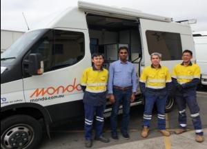 Cable testing team members standing in front of van.